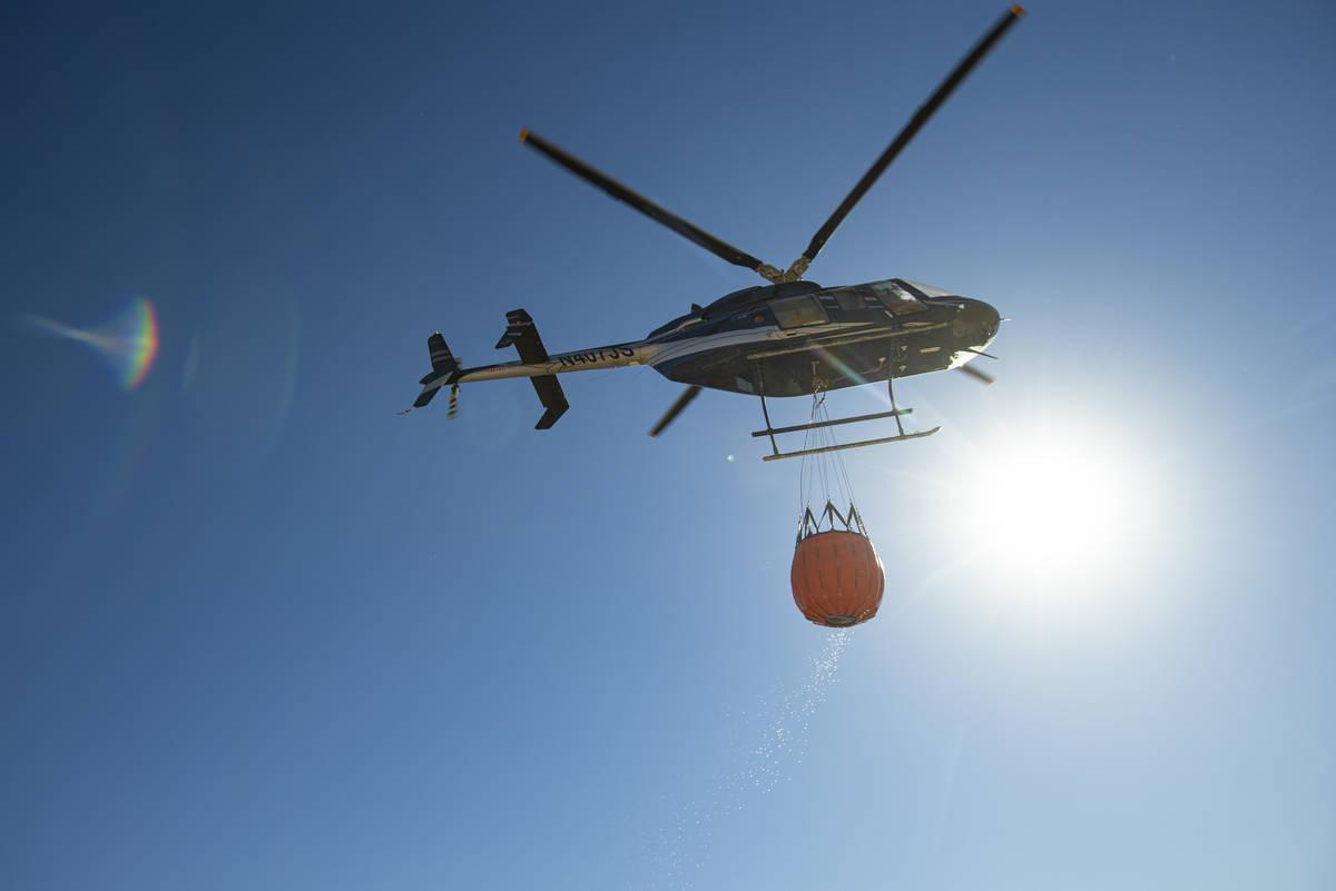 Rick Thielmann, chief pilot at the Nevada Department of Wildlife, hauls water using a Bambi buc ...