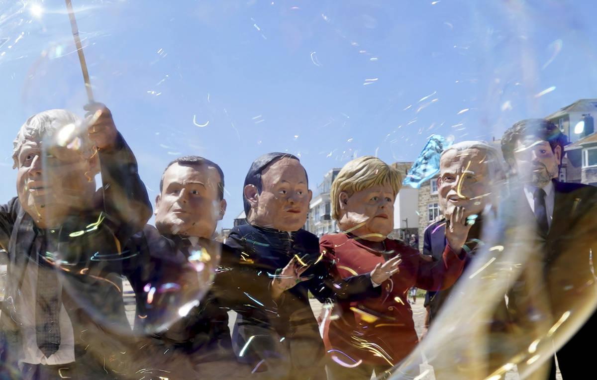 Manifestantes llevan cabezas gigantes que representan a los líderes del G7 mientras juegan con ...