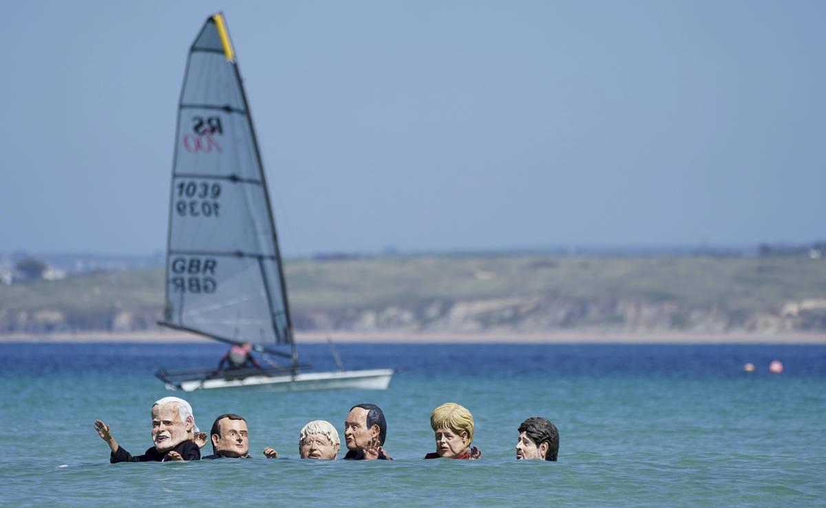 Manifestantes con cabezas gigantes que representan a los líderes del G7 nadan en el agua duran ...