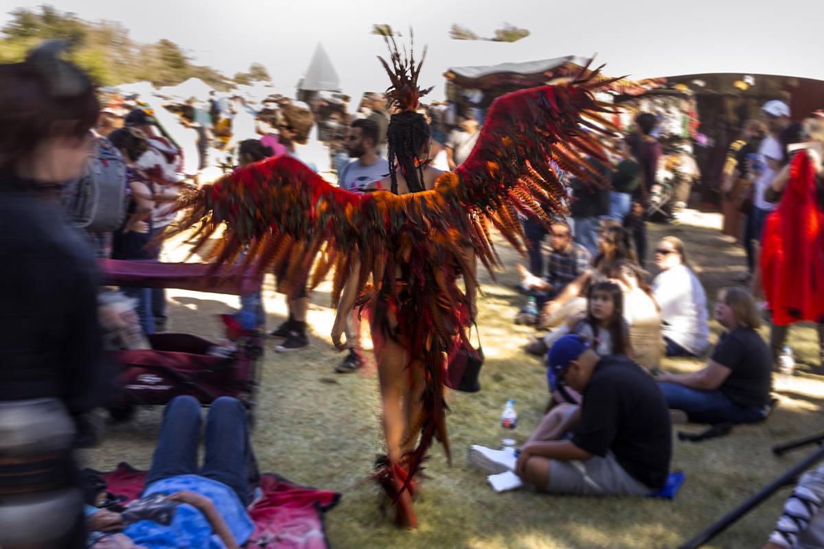 Una asistente disfrazada de pájaro se abre paso entre la multitud durante el Age of Chivalry R ...