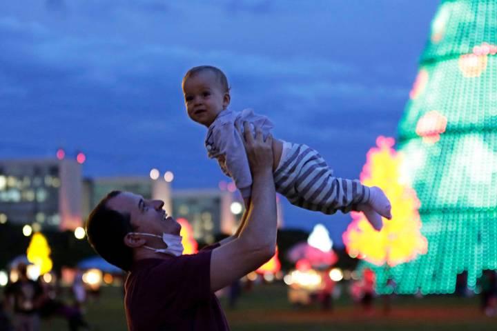 En esta foto de archivo, un padre con su cubrebocas hacia abajo, juega con su hijo en la Explan ...