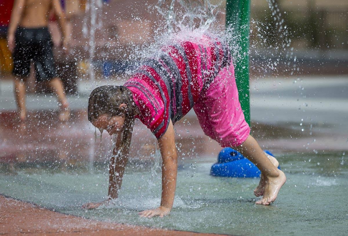 Ellie Bagenski, de siete años, de Baker City, Oregón, es golpeada con agua en el chapoteadero ...
