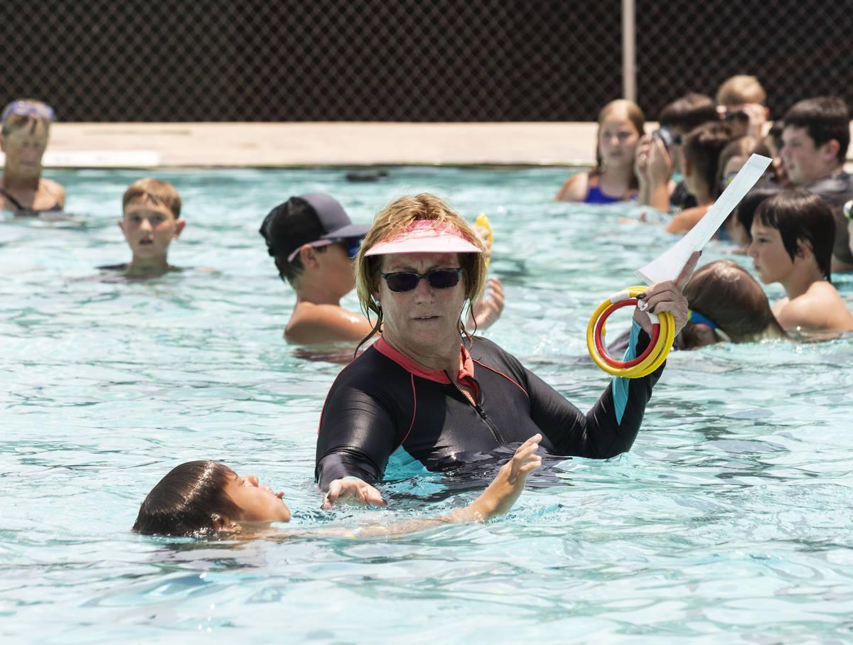 Kim Tyler, instructora voluntaria, observa cómo los niños nadan durante la 12ª Lección de n ...