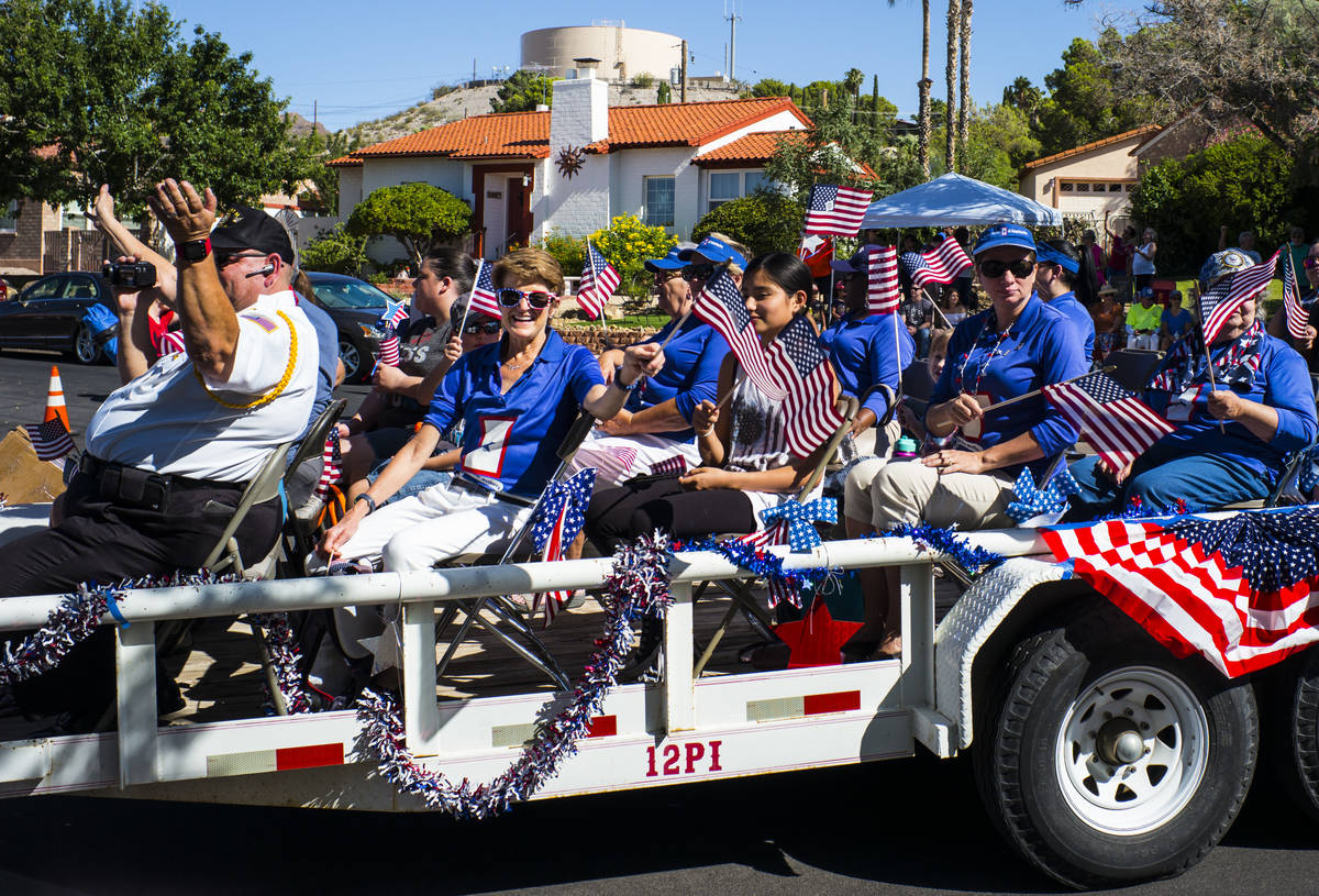 Asistentes al desfile saludan a los espectadores en la multitud durante el 25º desfile patrió ...