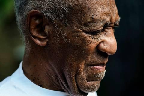 Bill Cosby escucha a los miembros de su equipo hablar durante una conferencia de prensa afuera ...