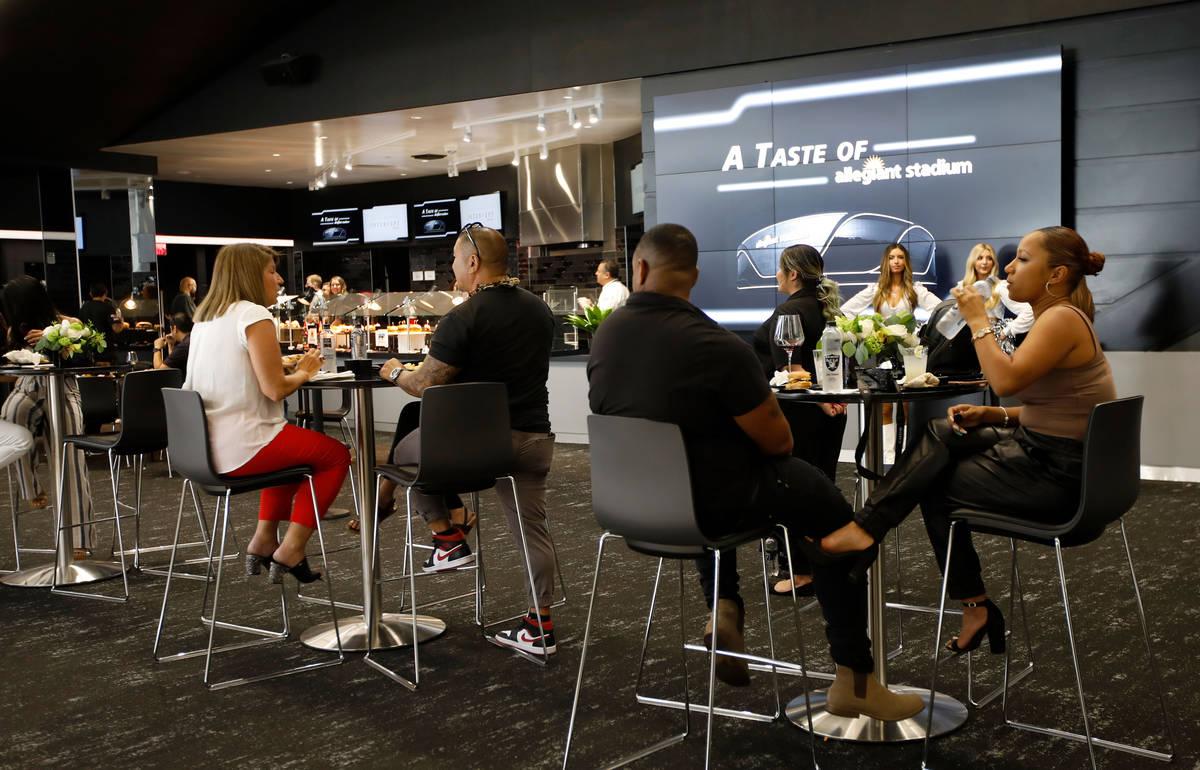 Los invitados disfrutan de comidas y bebidas durante un evento de experiencia gastronómica en ...