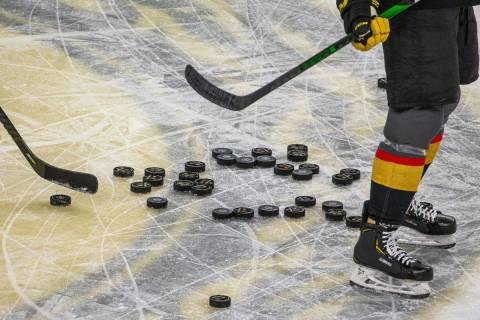 Pucks se apilan en el hielo mientras los Vegas Golden Knights calientan antes del primer period ...