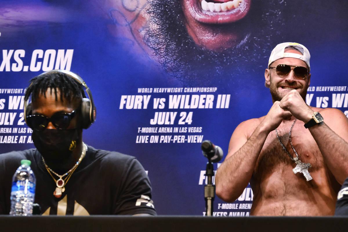 El campeón de los pesos pesados del CMB, Tyson Fury, a la derecha, levanta los puños mientras ...
