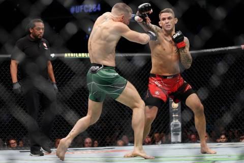 Conor McGregor, izquierda, y Dustin Poirier, pelean en la primera ronda de una pelea de peso li ...