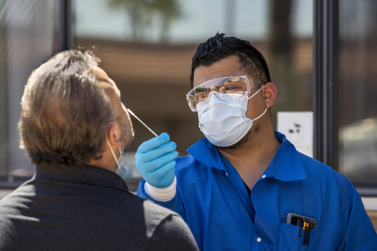 José Tirana realiza una prueba de COVID-19 a un paciente en Sahara West Urgent Care & Wellness ...