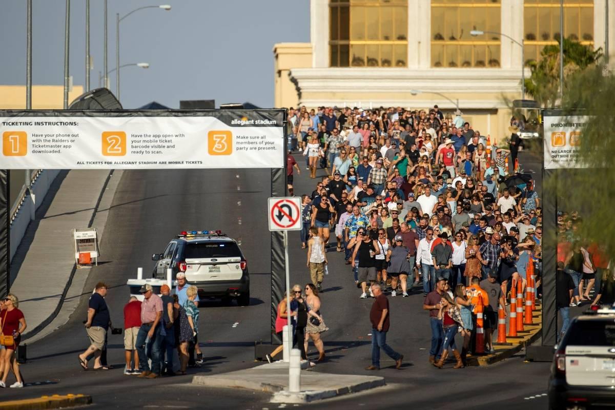 Fans caminan a través del paso elevado de Hacienda bajo el calor para el concierto de Garth Br ...