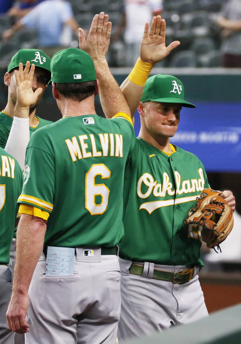 El gerente de los Oakland Athletics, Bob Melvin, a la izquierda, choca los cinco con Matt Chapm ...