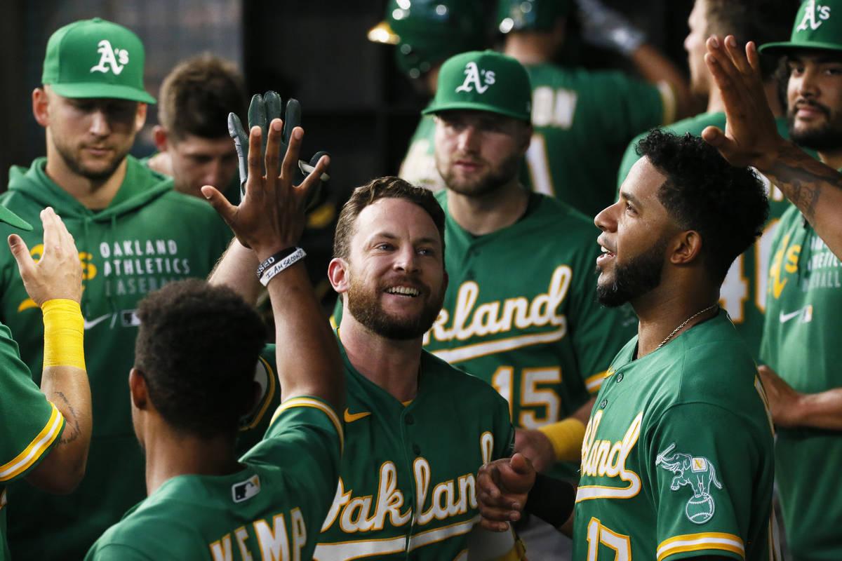 Jed Lowrie, de los Oakland Athletics, es saludado en el dugout después de batear un jonrón co ...