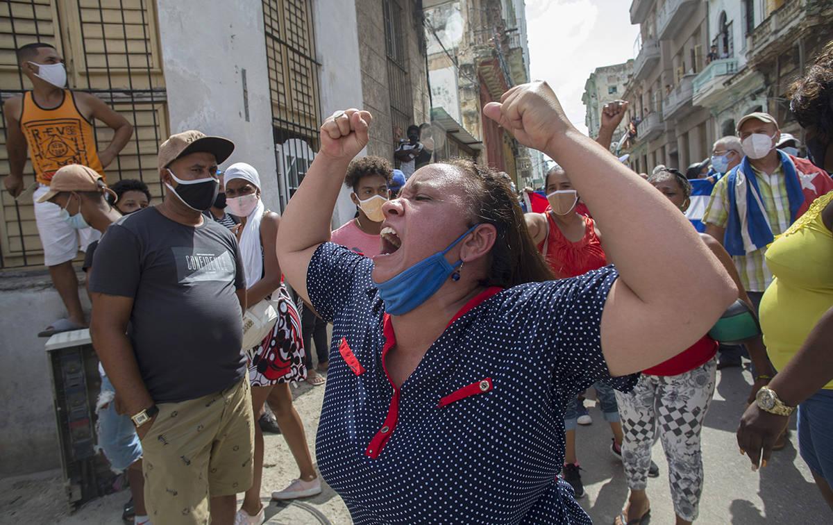 Una mujer grita consignas progubernamentales mientras manifestantes antigubernamentales marchan ...