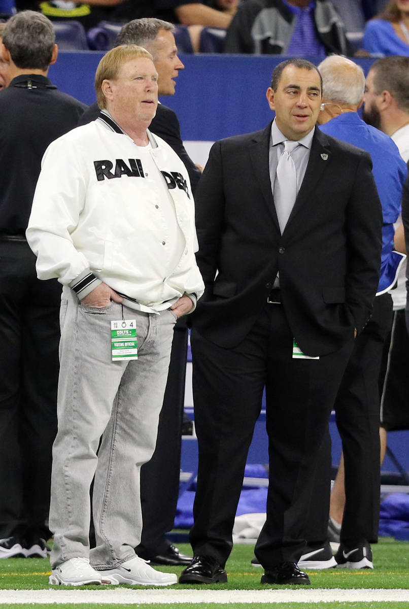 El propietario de los Raiders, Mark Davis, a la izquierda, habla en la línea de banda con el v ...