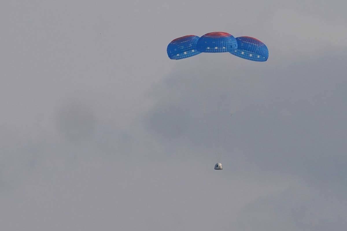 La cápsula New Shepard de Blue Origin desciende en paracaídas de forma segura hasta la zona d ...