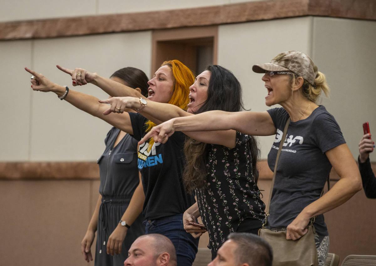 Miembros del público expresan su descontento mientras los oficiales escoltan a Katrin Ivanoff ...