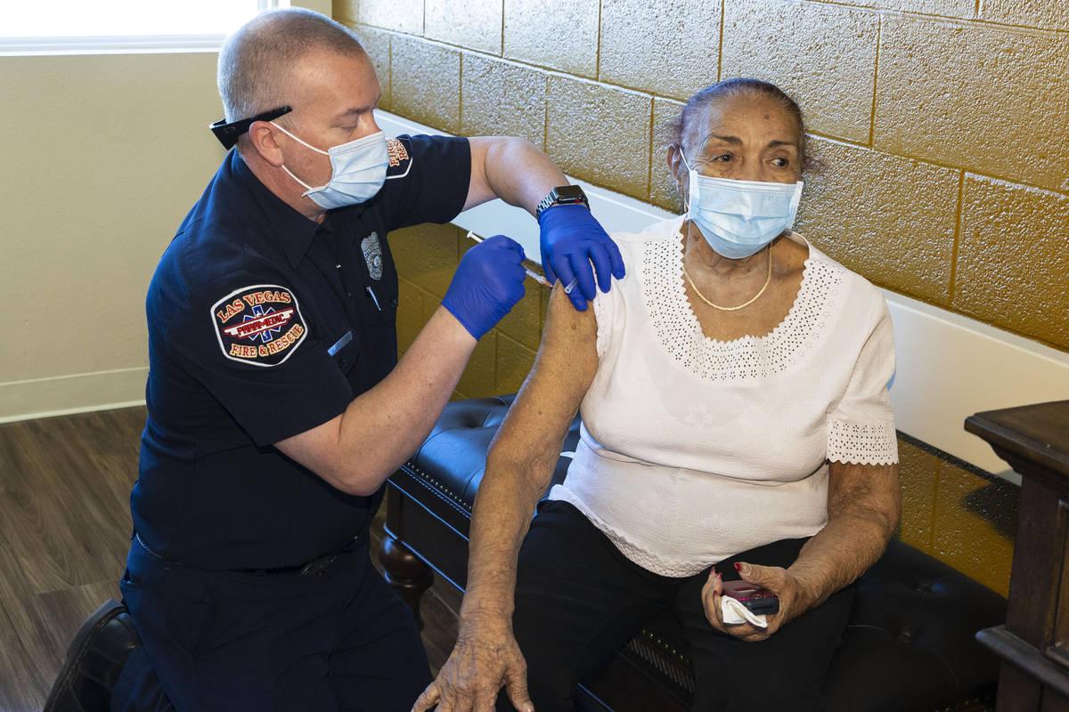 Chris Racine, del Las Vegas Fire Rescue, administra la vacuna contra COVID-19 a la residente de ...