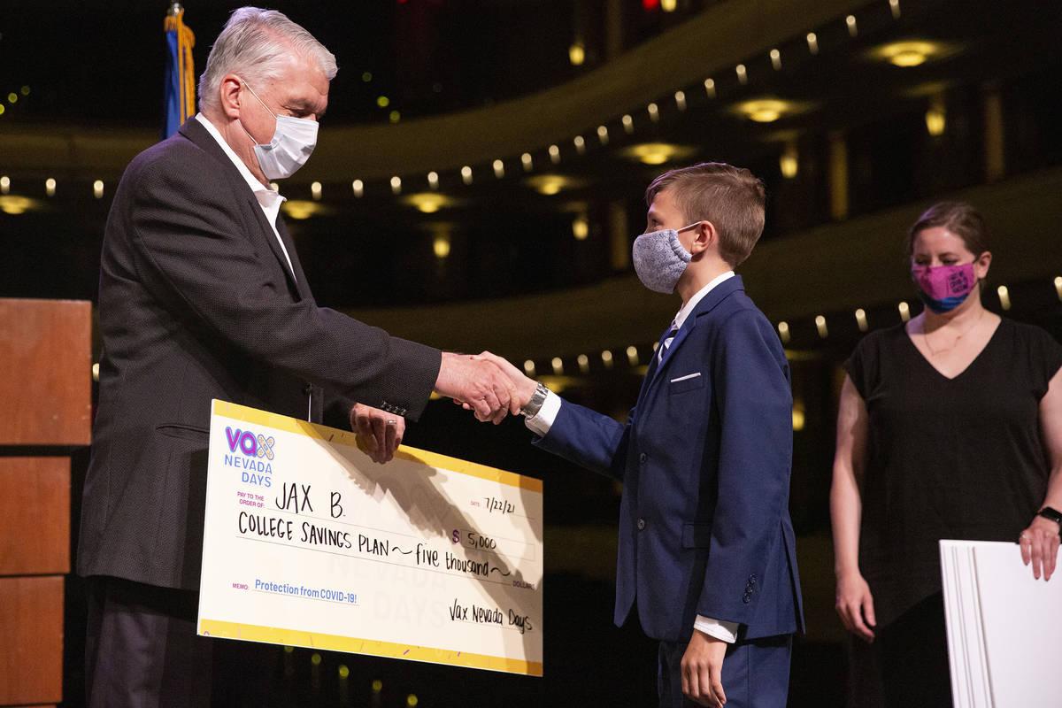 El gobernador Steve Sisolak estrecha la mano de Jax B. después de que ganara un plan de ahorro ...
