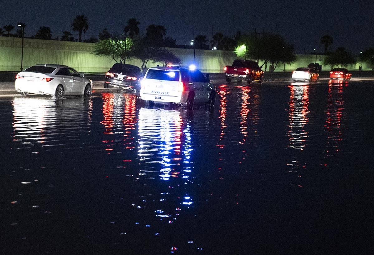 Automovilistas navegan a través de la calle inundada de St. Rose Parkway y Eastern Avenue, el ...