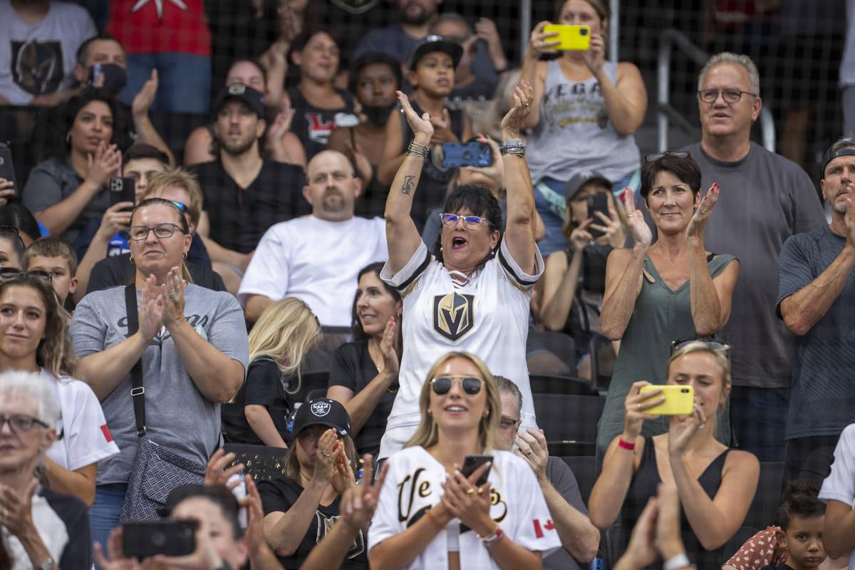Fans animan a los jugadores durante un partido de softball benéfico en el que participan compa ...