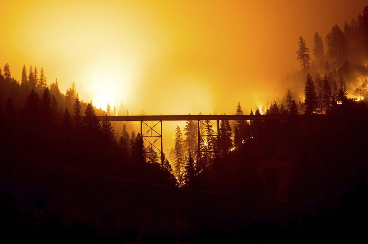 Visto en una fotografía de larga exposición, el Dixie Fire arde detrás de un puente en el Co ...