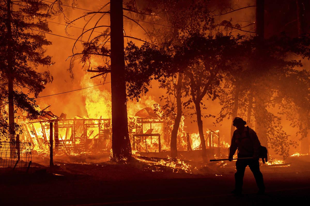 Un bombero pasa por delante de una casa en llamas mientras el Dixie Fire incendia el Condado Pl ...