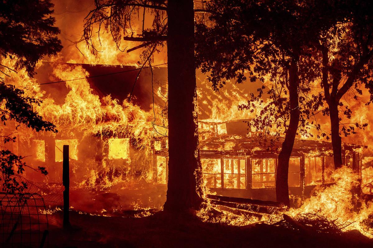 Las llamas del Dixie Fire consumen una casa en la comunidad de Indian Falls del Condado Plumas, ...