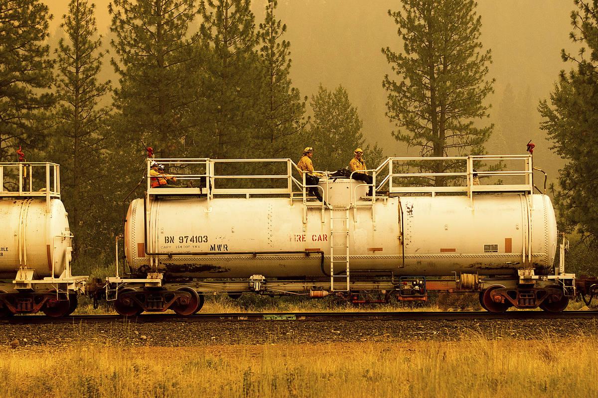 Bomberos viajan sobre un tren de bomberos mientras luchan contra el Dixie Fire en el Condado Pl ...