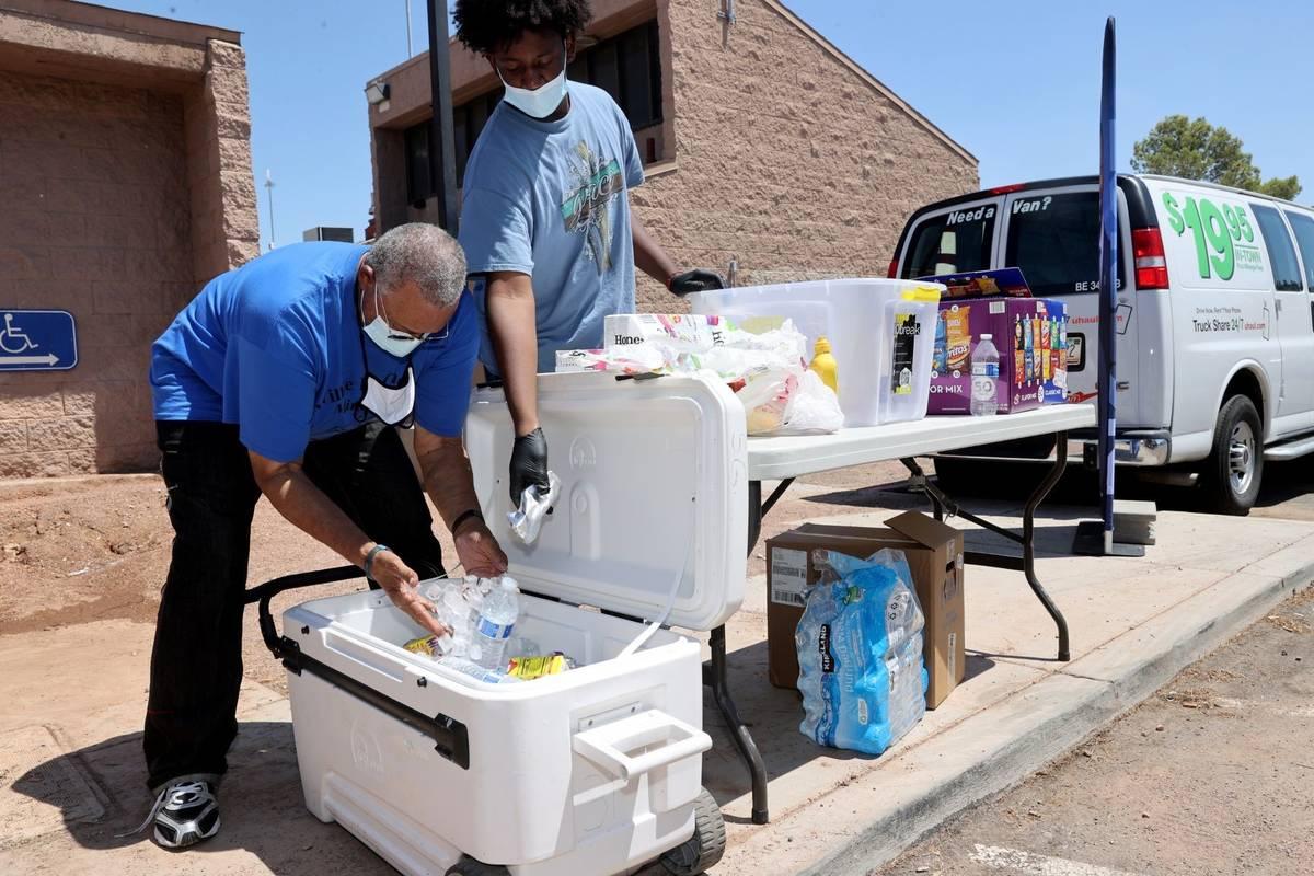 Willie Cherry y su nieto Jailin Cherry, de 16 años, entregan bebidas gratis durante un evento ...