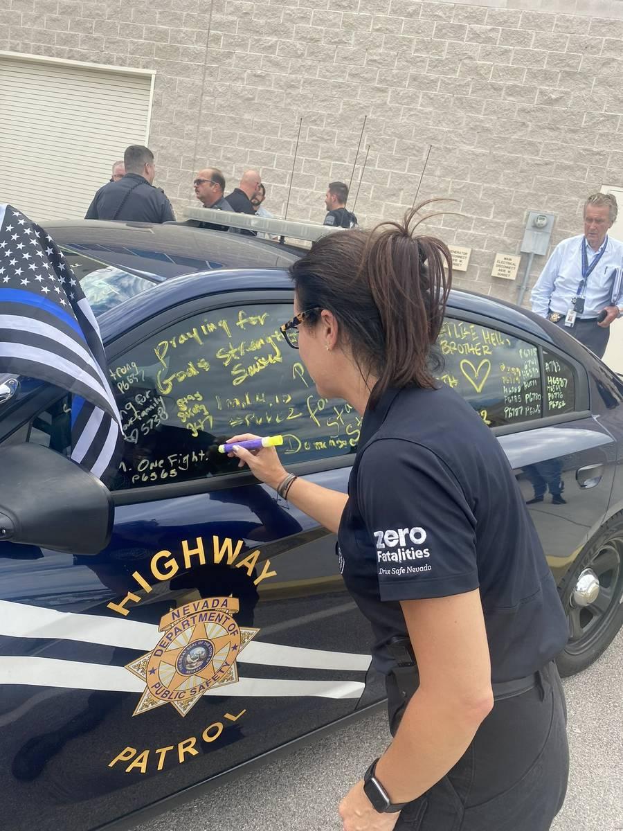 Miembros del Nevada Department of Public Safety firman el coche patrulla del soldado Micah May, ...