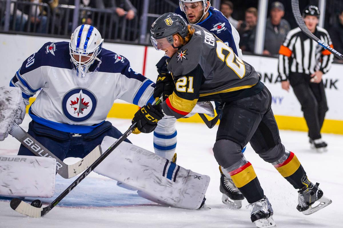 El portero de los Winnipeg Jets, Laurent Brossoit (30), usa su almohadilla contra un tiro del c ...