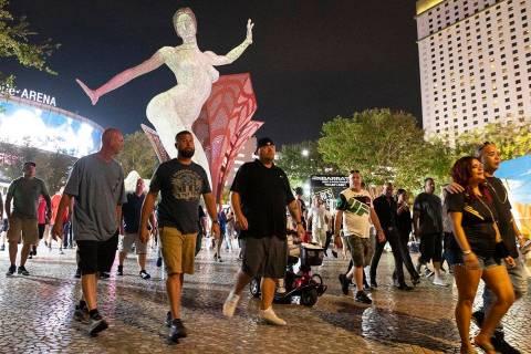Gente, casi toda sin cubrebocas, caminan cerca de T-Mobile Arena, el sábado 10 de julio de 202 ...