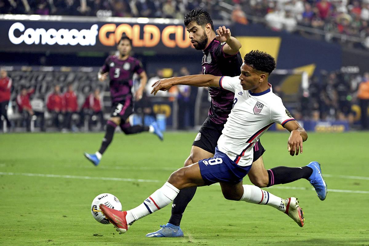 El jugador estadounidense, Nicholas Gioacchini (8), alcanza el balón contra el defensor mexica ...