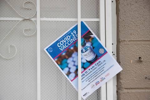 Un folleto informativo sobre la vacunación contra COVID-19 colocado en la puerta de un complej ...