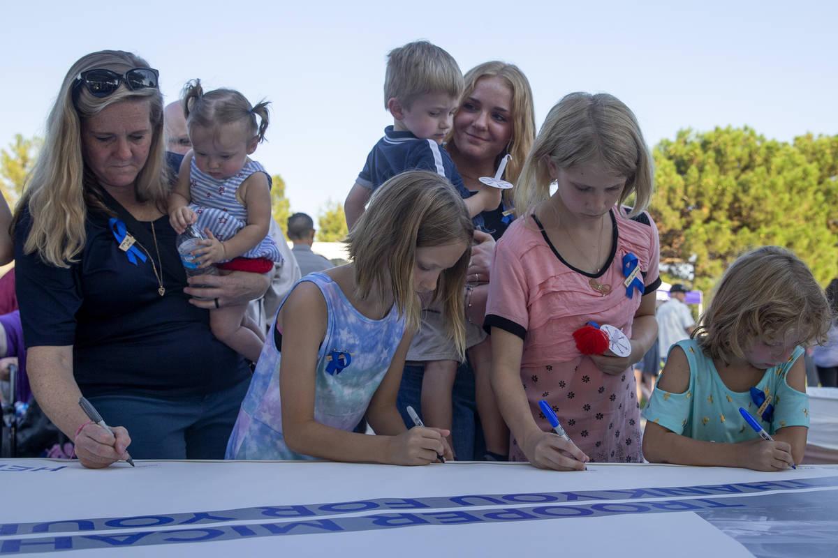 Familiares sostienen a los hijos del agente de la NHP Micah May, Melody May, a la izquierda, y ...