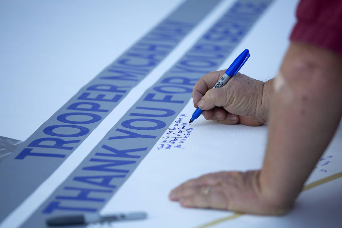 Familiares, amigos y compañeros de trabajo firman una pancarta para el agente de la NHP caído ...
