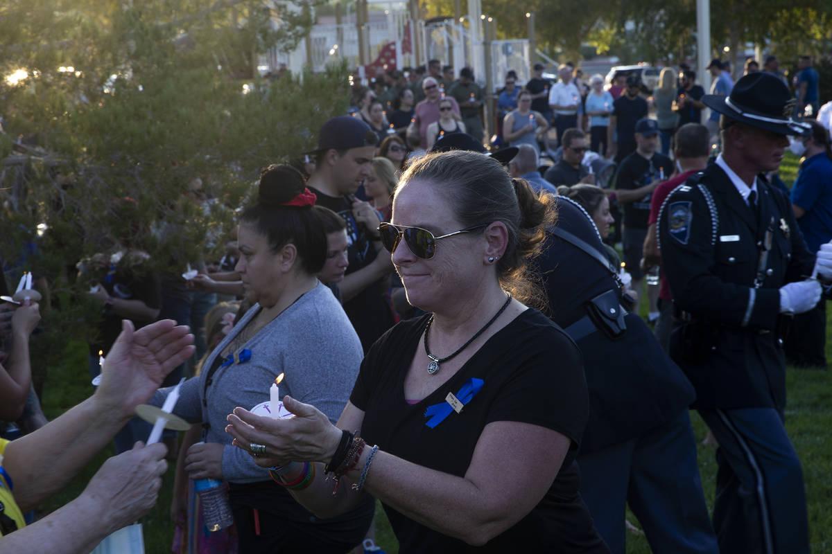 Lauren Hamilton, cuya esposa es miembro de la NHP, ayuda a encender las velas en una vigilia po ...