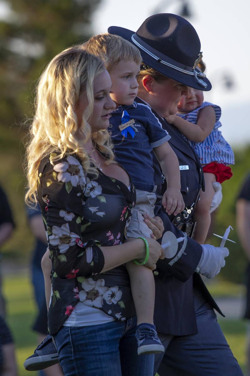 Joanna May sostiene a su hijo Raylan May mientras un miembro de la Guardia de Honor lleva a su ...