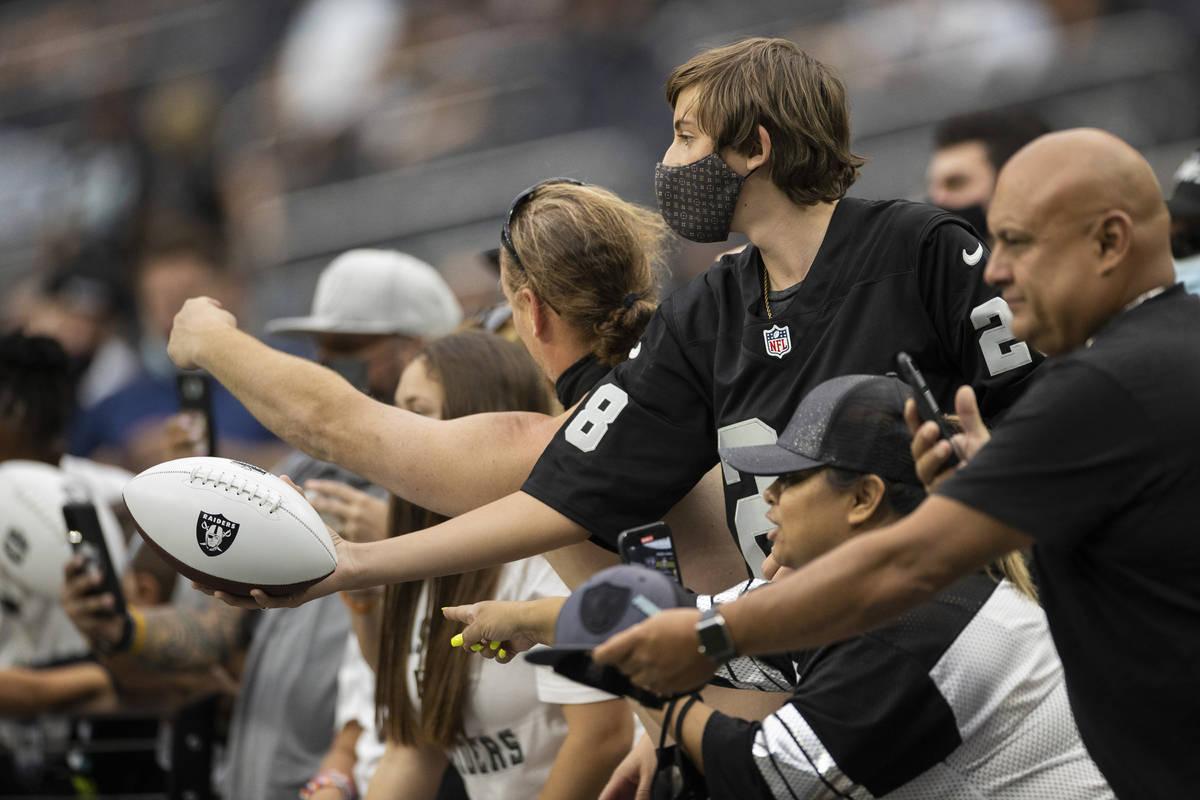 Fans de los Raiders participan en la acción durante una práctica especial del campo de entren ...