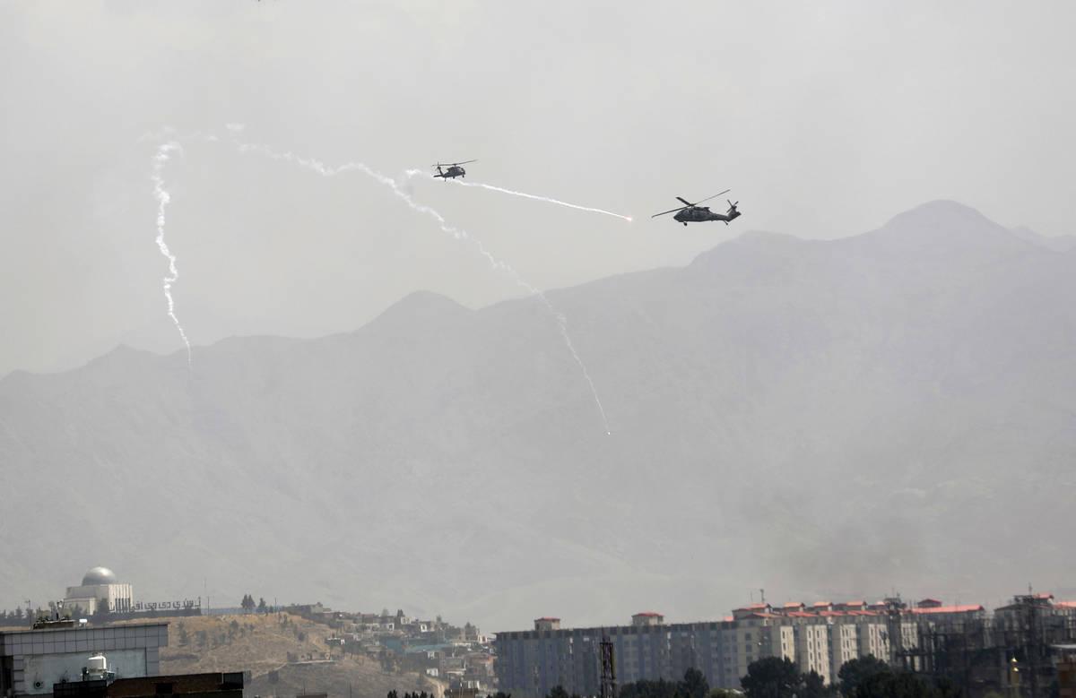 Se despliegan bengalas de señuelo antimisiles mientras helicópteros militares Black Hawk de E ...