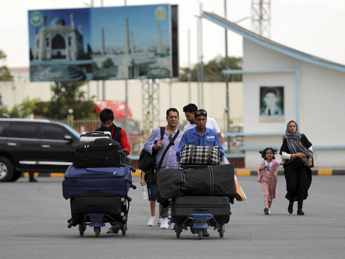 Pasajeros caminan hacia la terminal de salidas del Aeropuerto Internacional Hamid Karzai en Kab ...