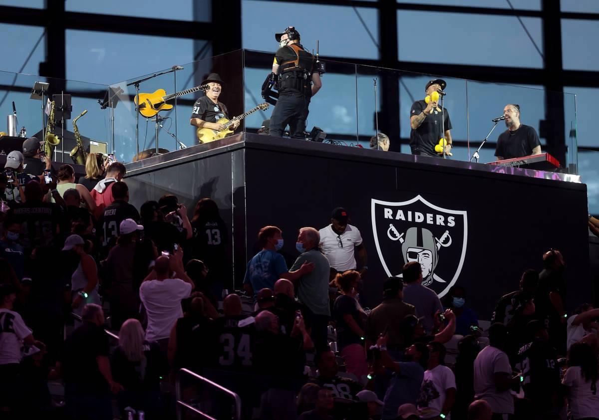 Carlos Santana, izquierda, actúa durante el medio tiempo del juego de pretemporada de la NFL, ...