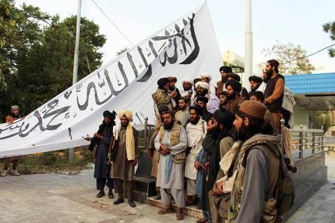 Combatientes talibanes posan para una fotografía mientras izan su bandera en la casa del gober ...