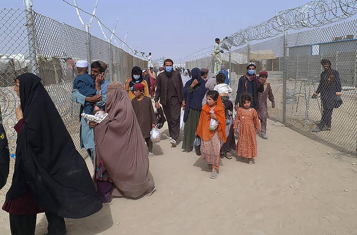 Los viajeros ingresan a Pakistán a través de un paso fronterizo en Chaman, Pakistán, el lune ...