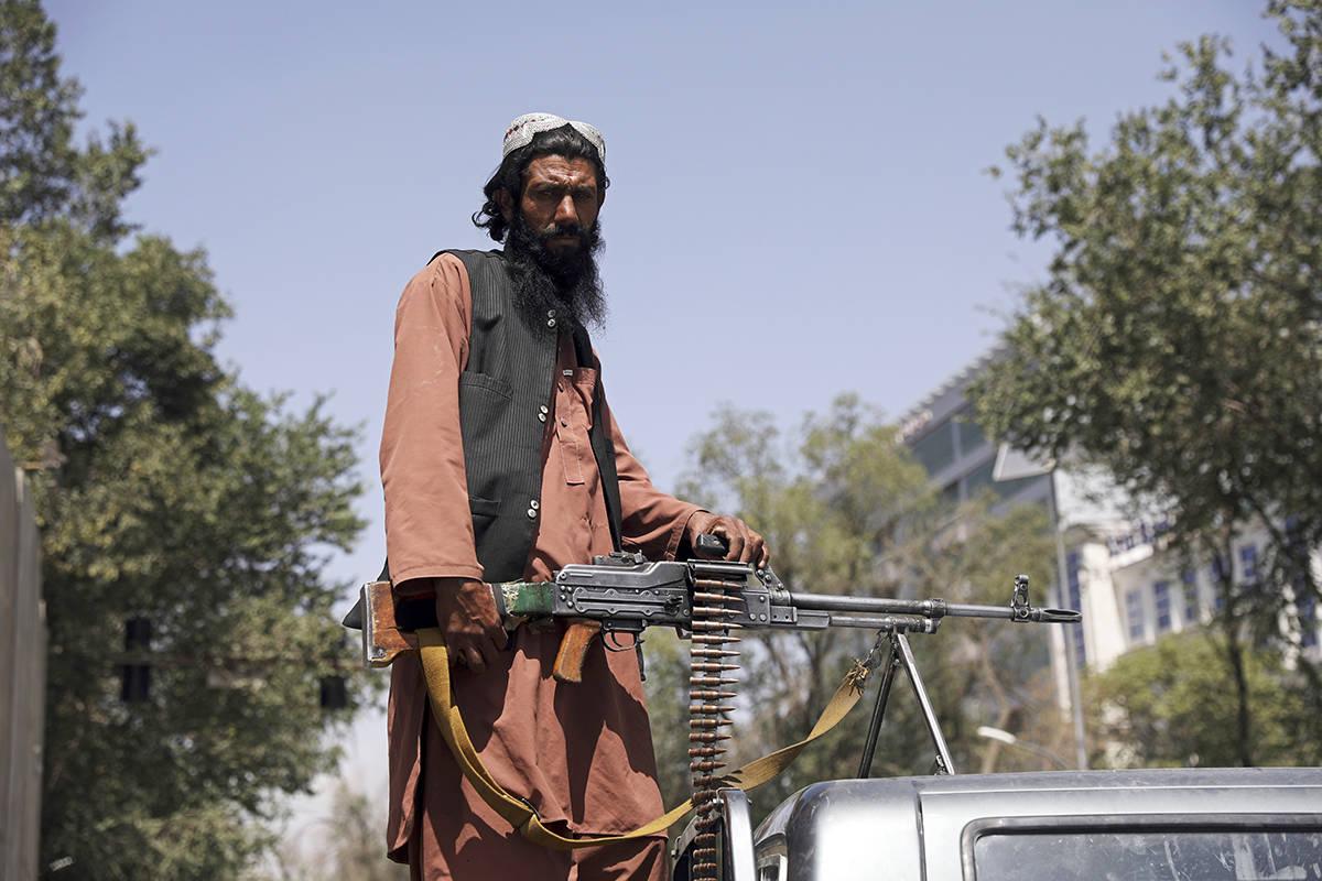 Un combatiente talibán monta guardia en la puerta principal que conduce al palacio presidencia ...