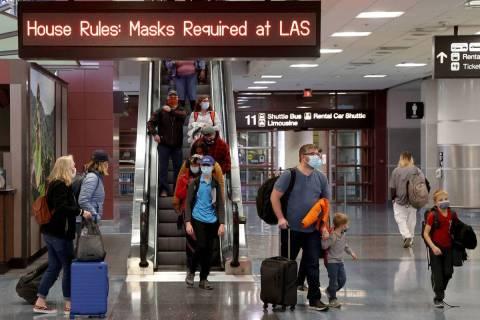 """En esta foto de archivo, viajeros """"enmascarados"""" caminan por la Terminal 1 del Aeropuerto Inter ..."""
