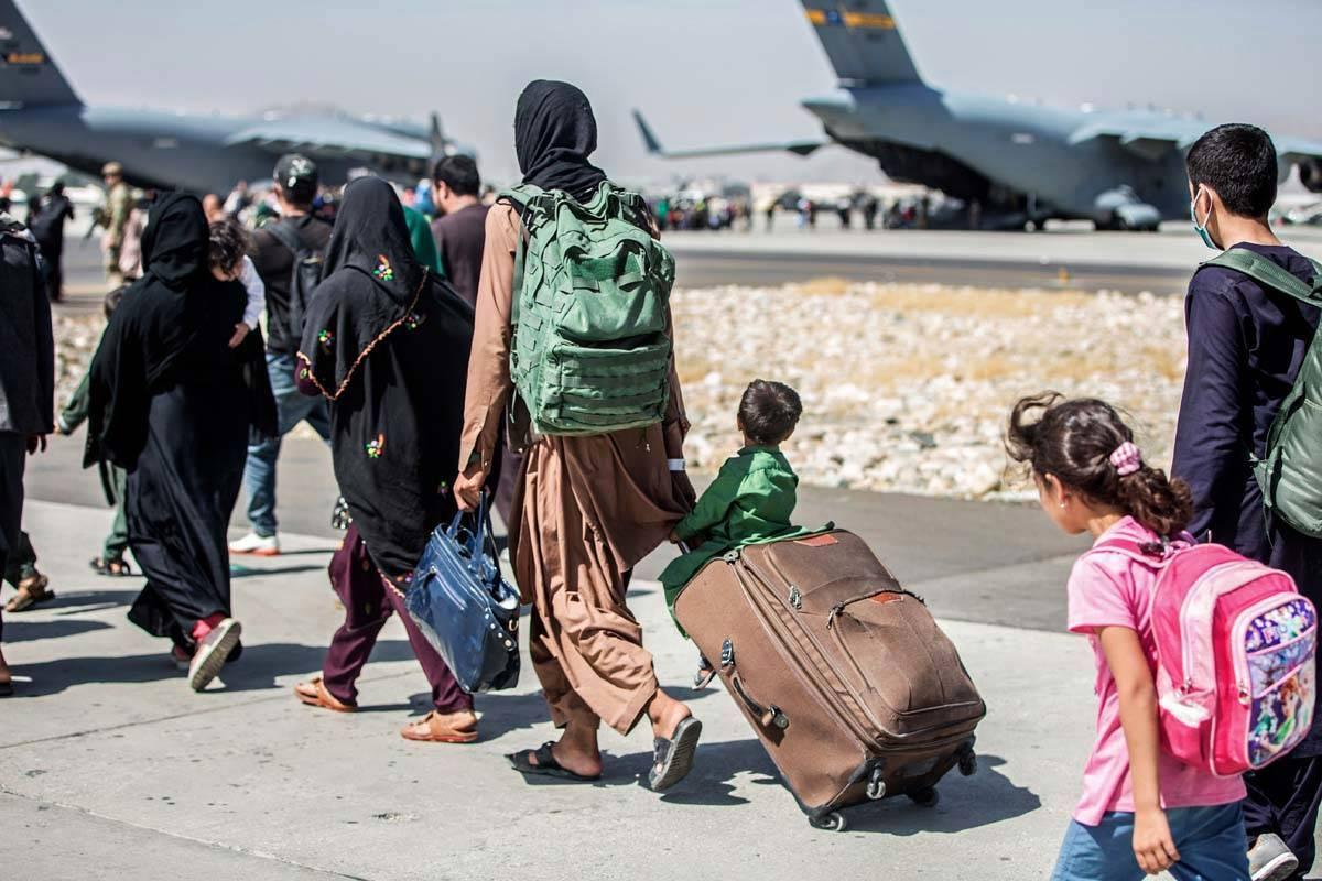 En esta imagen proporcionada por el Cuerpo de Marines de EE.UU., las familias caminan hacia su ...