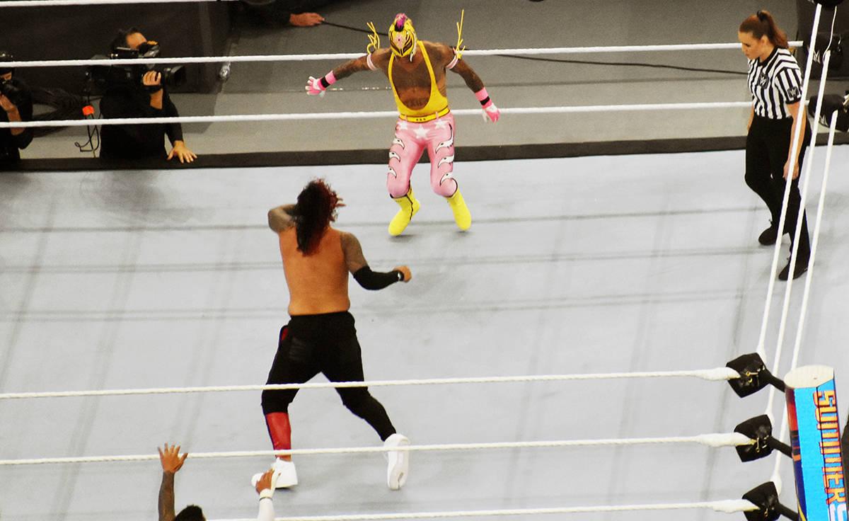 Rey Mysterio, vestido de rosa con amarillo, peleando contra Jimmy Usos. El sábado 21 de agosto ...