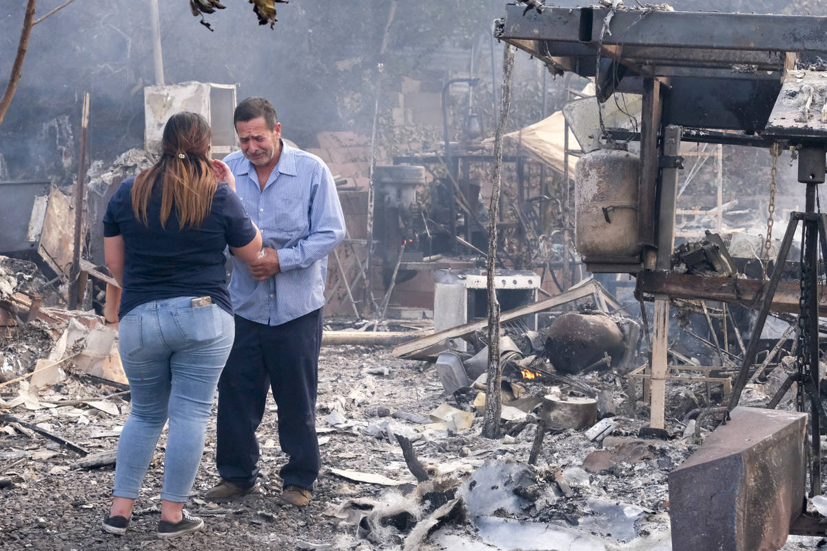 José Lamas, a la derecha, y su hija Astrid Covarrubias inspeccionan los restos carbonizados qu ...